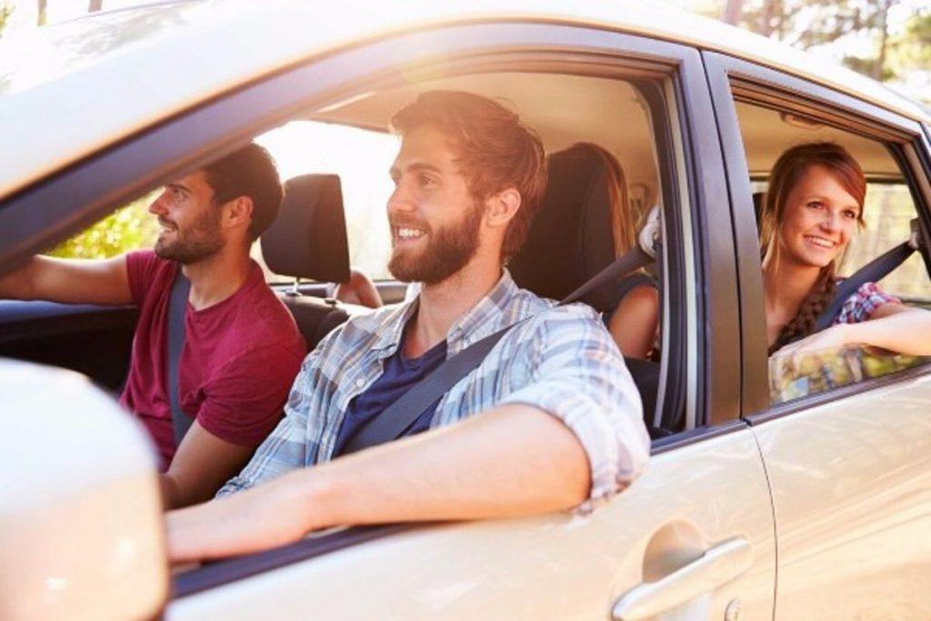 Jóvenes abordo de un automóvil sonriendo.