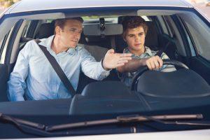 Adulto enseñando a conducir a un joven en un carro nuevo.