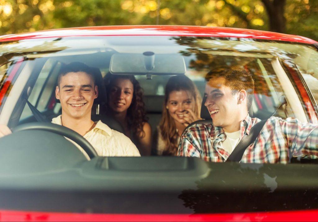 Grupo de jóvenes a bordo de un automóvil.