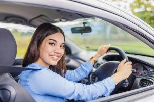 Mujer conduce un coche gris.
