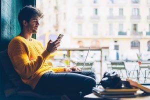 Joven sentado en su sala revisando su celular.