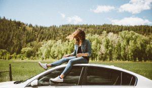 Una chica se encuentra sentada en el techo de su automóvil.