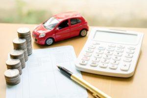 Sobre una mesa se encuentra un auto color rojo a escala, una calculadora, papel y pluma.