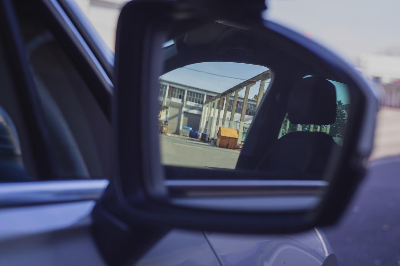 persona viendo por el espejo del auto