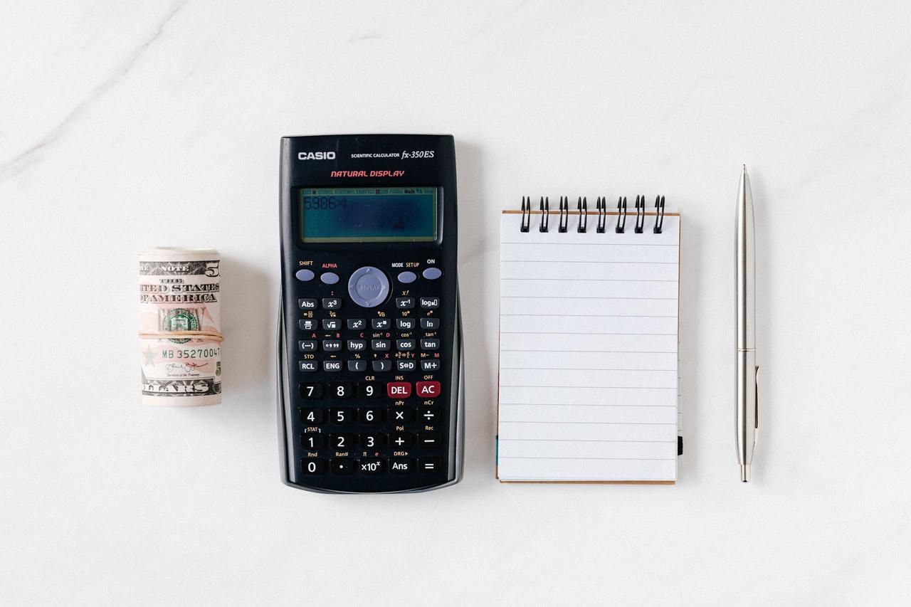 calculadora, libreta y dinero ahorrado