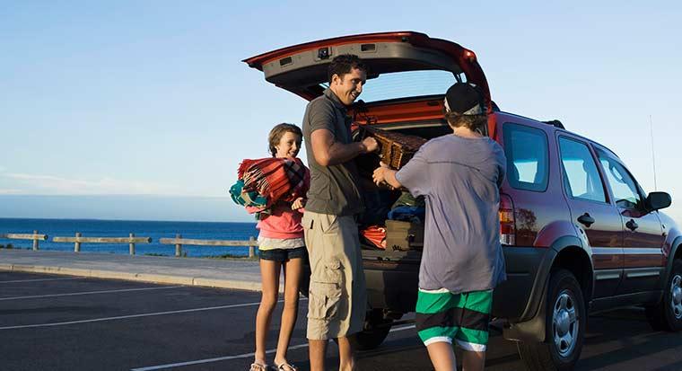 familia llegando a la playa con su coche nuevo